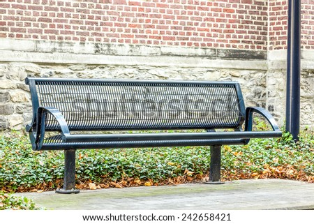 on an platform there is an iron street bench where you can rest cozy - stock photo