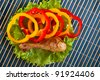 on blue bamboo napkin with plate of food: Lettuce, they cut slices sweet Bulgarian pepper and fried, very tasty-looking chicken drumstick-top view - stock photo