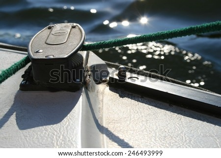 On deck of a sailing boat a green rope is pulled around a idler pulley as commonly used to tighten a sail - stock photo