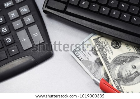 on desk in office, calculator, computer dollars lie on the table