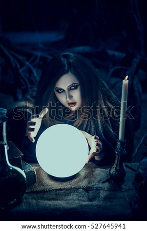On eve of Halloween witch casts a spell, uttering terrible incantations on a glowing, crystal ball. Fairytale spooky voodoo shack.Fabulous and mystical concept.Fashionable toning.Creative color.