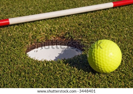 On ground flagstick and green golf ball near hole - stock photo