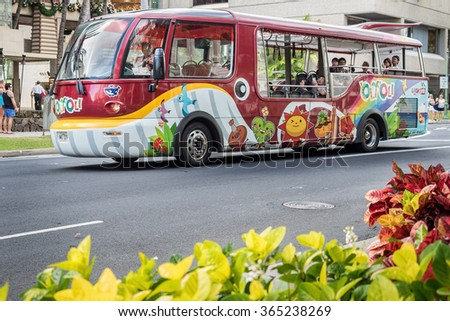 On Kalakaua Avenue, Honolulu, Hawaii, USA - December 10, 2015: Standing along the avenue, a unique-looking tourist shuttle bus, with colorful designs, drove by.
