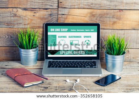 On line shop website template design on a laptop. Office desk. - stock photo