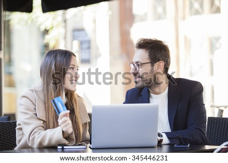 On line shopping. Happy couple using credit card to internet shop on-line. Young couple with Laptop Computer and Credit Card buying on line. - stock photo