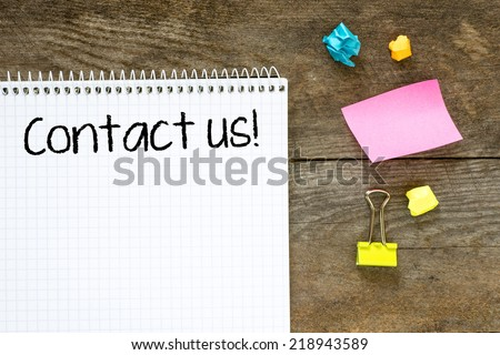 On note paper wooden wall with the words Contact Us on it - stock photo