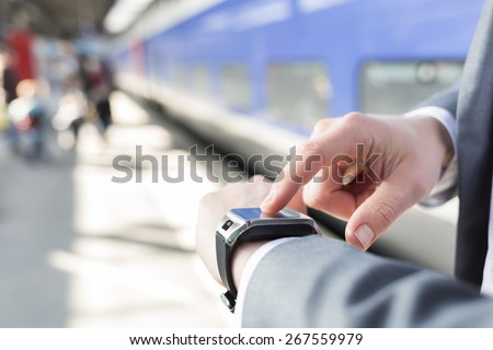On platform station a man using his smartwatch. Close-up hands - stock photo