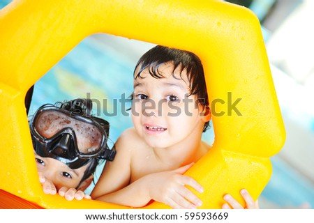 On pool, two kids playing with toys - stock photo