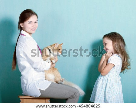 on reception at the vet.little girl tenderly looks at his cat who sits in the hands of a veterinarian.toned  - stock photo