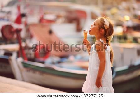 On seacoast the girl eats ice-cream at yachts background - stock photo