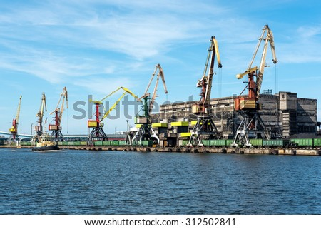 On-shore coal cargo terminal with heavy lifting cranes - stock photo