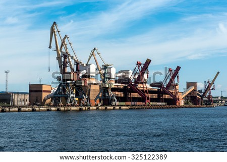 On-shore coal cargo terminal with two lifting cranes and a heavy duty conveyor - stock photo