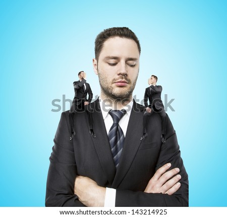 on shoulders of a businessman siting two little man, and whispers in my ear - stock photo
