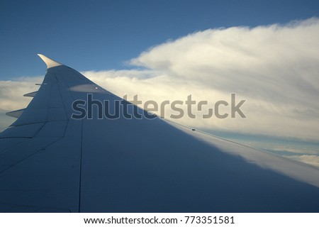 On the aircraft looking through the window during flying, beautiful blue sky and cloudy