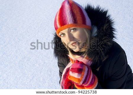 on the background of snow, a beautiful girl in a cap - stock photo