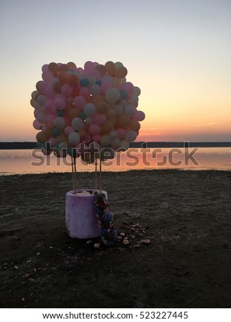 on the banks of the gentle balloons tied to a basket and flowers