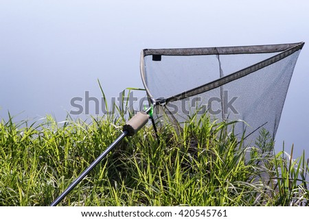On the banks of the river lowered into the water great convenient the net for caught fish. - stock photo