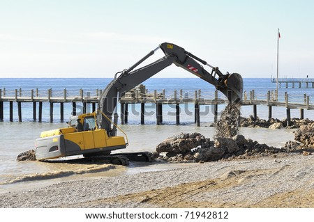 On the beach in Antalya, rebuilding the rock beach. - stock photo