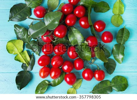 On the blue wooden table cherry tomatoes on a branch and lime leaves