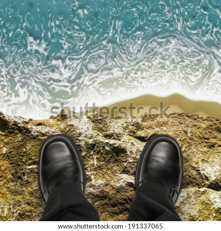 On the edge concept with man standing on cliff ledge looking down at ocean - stock photo
