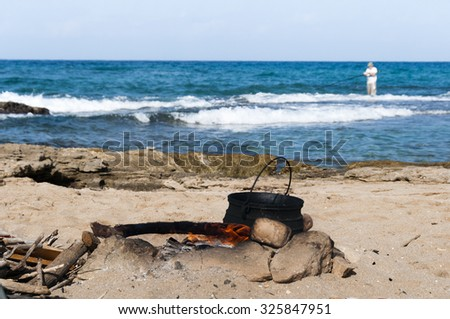 On the fire, fenced with stones in a large pot preparing ear and fisherman continue fishing rod to catch fish - stock photo