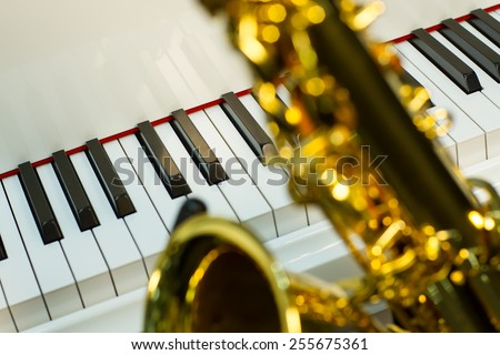 on the foreground of sax shining on the background a white grand piano - stock photo