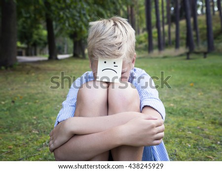 On the forehead shows drawn cry icon on yellow stickers. Concept of sad thoughts and negative emotions. Crying boy sits on green grass in a forest.   - stock photo