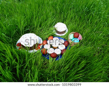 On the green grass on plates lies Easter food, cakes, painted eggs. Easter brunch Spring. Easter. The Feast of Easter. Holy Sunday.
