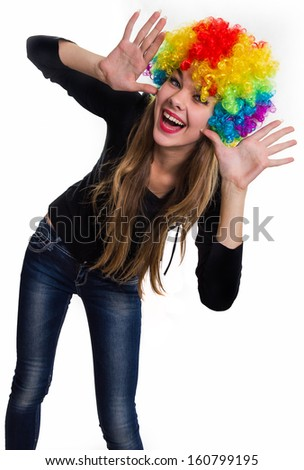 On the head of the cheerful girl multi-colored wig. Isolated on white. - stock photo