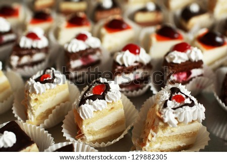 On the holiday table small cakes with different stuffing - stock photo