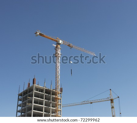 On the image there are two cranes on the  building. - stock photo