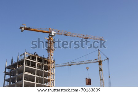 On the image there are two cranes. They ; construct   house. - stock photo