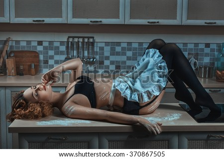 On the kitchen table lies a woman in an apron. On her underwear, and his body smeared with flour. - stock photo