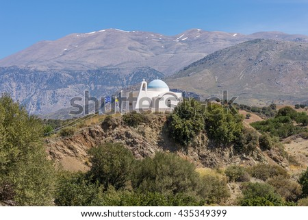 On the old road to Rethymno. White greek orthodox church in the foothills of the Ida mountains on Crete. In the Background the Psiloritis, the highest mountain on Crete. - stock photo