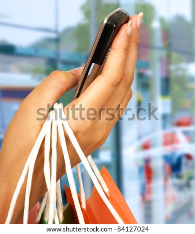 On The Phone After A Shopping Spree With Mall Windows Background
