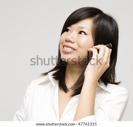 On the phone. Asian business woman on the phone, looking at side.