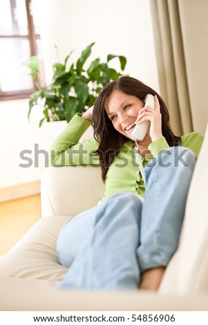 On the phone home: Happy woman calling, plant in background - stock photo