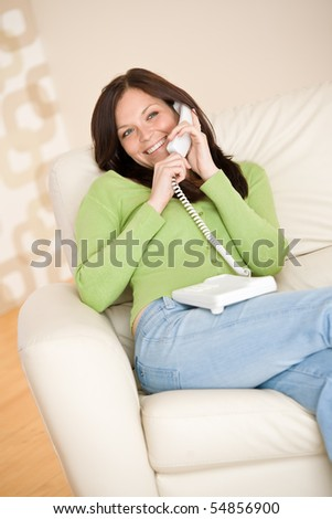 On the phone home: Smiling woman calling in living room