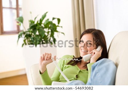On the phone home: Smiling woman calling in lounge, plant in background - stock photo