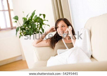 On the phone home: woman calling in living room - stock photo