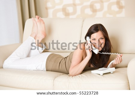 On the phone: young woman calling in lounge, lying down on sofa - stock photo