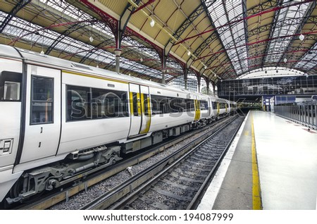 On the platform - Stock Image. Train Station, Modern Commuter Train inside the Victoria Railway Station in London, Europe. - stock photo