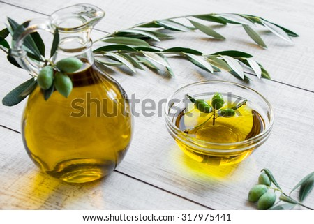 On the right bottle of olive oil to the left bowl with olive oil and olives on the white background of olive tree branches. Olive oil on the white. Horizontal shot. Daylight.   - stock photo