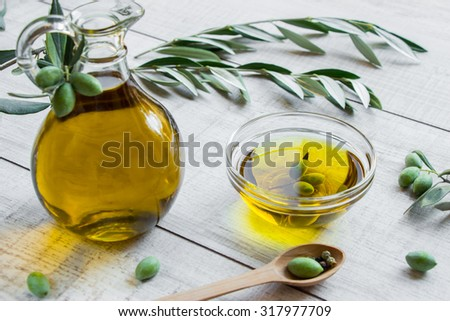 On the right bottle of olive oil to the left bowl with olive oil and olives on the white background of olive tree branches, olives and spoon with olive. Olive oil and olives. Horizontal. Daylight.   - stock photo