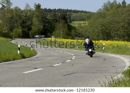 On the road. Motorcycle on the rural road. Blooming yellow field next to the road.  Switzerland - stock photo