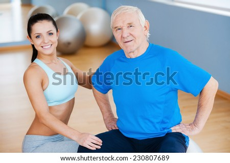 On the road to full recovery. Confident female physical therapist looking at camera and smiling while sitting close to cheerful senior man