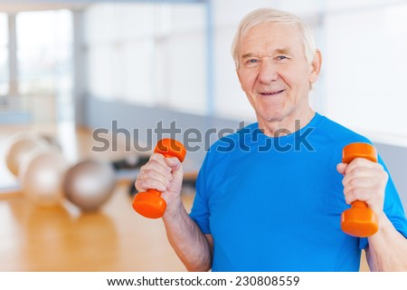 On the road to recovery. Happy senior man exercising with dumbbells and smiling while standing indoors  - stock photo