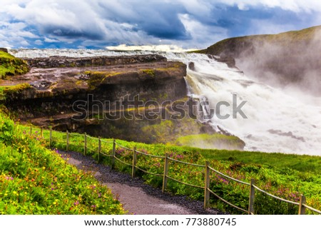 On the shore of the waterfall is a path for tourists. Incredible Golden Falls - Gulfoss in Iceland. Windy and cloudy summer day. The concept of extreme and phototourism