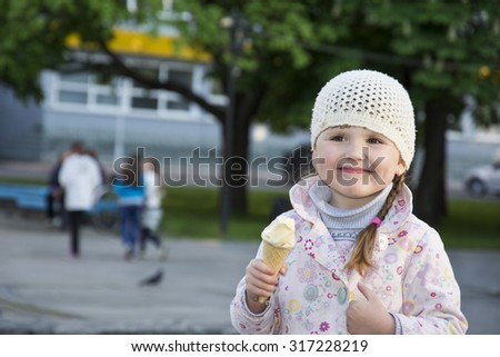 On the street in the spring of little cute girl holding an ice cream in her hand and smiling. - stock photo