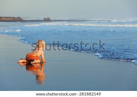On the sunset beach funny baby crawling on black wet sand to sea surf for swimming in the waves. Family lifestyle, and water activity during summer vacation with child on the tropical Bali island - stock photo